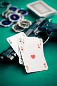 poker cards and handgun on green table