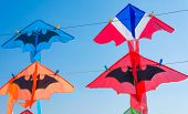 stock photo of kites  - Thailand flag color kite and bat kites hanging on string against blue sky - JPG