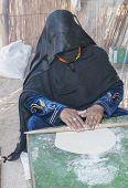 stock photo of burka  - Egyptian bedouin woman making traditional bread in the desert - JPG