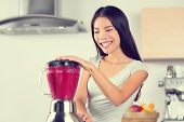 Smoothie woman making fruit smoothies with blender. Healthy eating lifestyle concept portrait of beautiful young woman preparing drink blending strawberries, raspberries and berries home in kitchen.