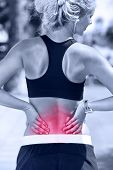 Back pain. Athletic running woman with injury in sportswear rubbing touching lower back muscles outside after exercising and training.