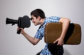Young Male Filmmaker With Old Movie Camera And A Suitcase In His Hand