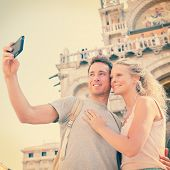 Selfie travel couple in love taking photo with smartphone, Venice, Italy, Piazza San Marco by Saint Mark's Basilica. Happy young couple on vacation in Europe. Woman and man in love traveling together