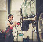 Serviceman unscrewing wheel in car workshop
