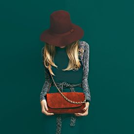 foto of green snake  - Lovely blond model in fashionable red hat and a red clutch on green background - JPG