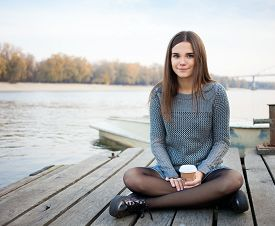 picture of jeans skirt  - Young beautful brunette woman in blouse and denim skirt sitting on the river pier with coffee and her smartphone - JPG