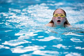 stock photo of breast-stroke  - Young girl in goggles and cap swimming breast stroke style in the blue water pool - JPG