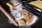 pic of pasta  - Metal pasta maker machine and ingredients for pasta on wooden background - JPG