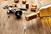 pic of merlot  - Glass bottle of wine with corks and corkscrew on wooden table background - JPG