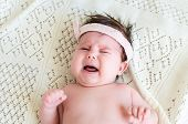 picture of cry  - Cute little crying newborn baby girl seeking attention with crying and screaming wearing in pink head bandage bow on her head on the background of woolen blanket - JPG