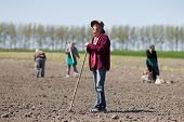 pic of hoe  - Senior peasant with hoe standing on fertile land other peasants in background - JPG