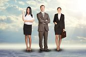 pic of coworkers  - Team leader stands with coworkers in background and in looking at camera on abstract background - JPG