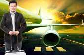 stock photo of air transport  - young business man and traveling luggage standing in front of passenger jet plane flying over airport runways use for people journey and air transport occupation - JPG
