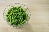 pic of threshing  - green pepper in bowl over wooden background - JPG
