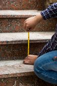 pic of measuring height  - Closeup shot of worker measuring height of stone steps - JPG