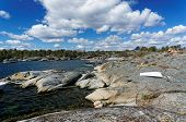 foto of puffy  - Rocky shore of a Norwegian fjord bay in the spring - JPG