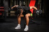 stock photo of bent over  - handsome young african descent mixed race man doing Seated Bent Over Dumbbell Reverse Fly workout in gym - JPG