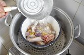 foto of boiling water  - Pouring boiled water to the raw chicken in the bowl - JPG