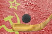 stock photo of hockey arena  - Hockey puck hockey stick and the image of the Soviet flag on the ice - JPG