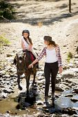 pic of horse-riders  - cute female kid jockey having fun learning riding pony outdoors happy with young Australian American horse instructor woman in cowboy look teaching the little rider in summer nature countryside - JPG