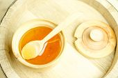 pic of cade  - Honey in a wooden bowl with a wooden spoon and lid - JPG