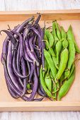 stock photo of bean-pod  - Young green and purple bean pods on wooden table - JPG