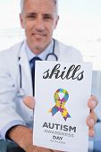 stock photo of prescription pad  - The word skills and portrait of a male doctor showing a blank prescription sheet against autism awareness day - JPG