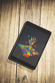 image of autism  - Autism awareness hand against overhead of tablet on desk - JPG