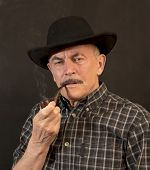 stock photo of hillbilly  - Cowboy in black hat with Pipe on a black background - JPG