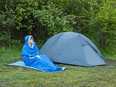 stock photo of sleeping bag  - The man is resting in a sleeping bag on the background of tents and green forests - JPG