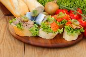 foto of baguette  - Baguette slices with herring salmon pollock and tuna garnished and topped with onions tomatoes pickles and salad - JPG