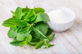 foto of zero  - fresh stevia leaves and small bowl with sugar on a white wooden table - JPG