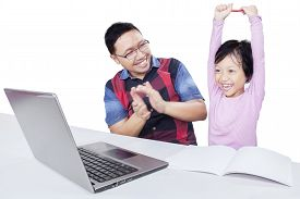 pic of applause  - Cheerful little girl raising hands with her dad giving applause after finishing her study with laptop isolated on white - JPG