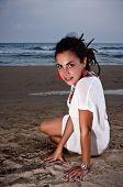 Girl in white dress sitting on Spanish beach