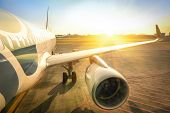 Airplane At Terminal Gate Ready For Takeoff - Modern International Airport During Sunset poster