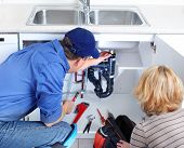 stock photo of plumber  - Mature plumber fixing a sink at kitchen - JPG