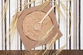 Постер, плакат: Wheat Bran In Bamboo Plate And Wooden Spoon With Wheat Ears