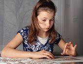 Teenage girl doing puzzle