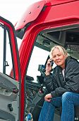 picture of big-rig  - Pretty blonde truck driver getting directions to a delivery site on her cellphone - JPG