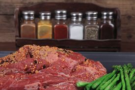 image of peppercorns  - meat raw beef fillet chunk on black tray asparagus on wooden table allspice pink white black green peppercorn stainless cutlery knife fork - JPG
