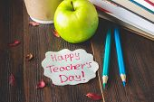 Concept Of Teachers Day. Objects On A Chalkboard Background. Books, Green Apple, Plaque: Happy Teac poster