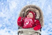 Baby In Stroller In Winter Park With Snow poster