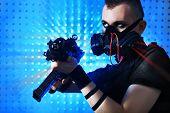 foto of skinheads  - Shot of a conceptual man in a respirator holding a gun - JPG