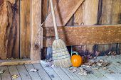 Straw Broom And Pumpkin In Rustic Wooden Old Barn Or Shed poster