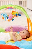 Baby girl lying on playmat, looking at toys.?