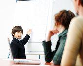 Niño genio en la presentación del negocio hablando con adultos y dándoles una conferencia