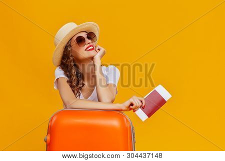 poster of Concept Of Travel. Happy Woman Girl With Suitcase And Passport On  Yellow Colored Background
