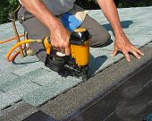 stock photo of shingle  - Carpenter uses nail gun to attach asphalt shingles to roof - JPG