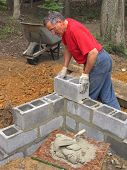 Man laying concrete block wall