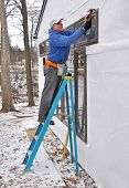 Carpenter installing windows in an addition